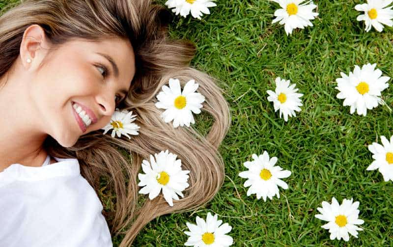 Happy blonde woman lying in a flower garden