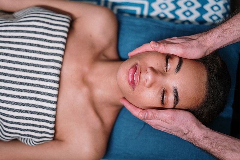 woman lying on blue textile while having face massage