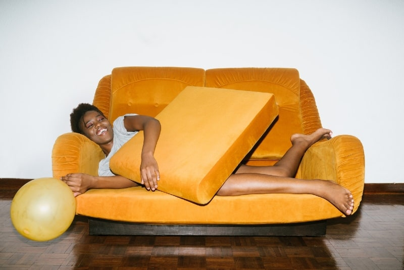 smiling woman lying on orange sofa