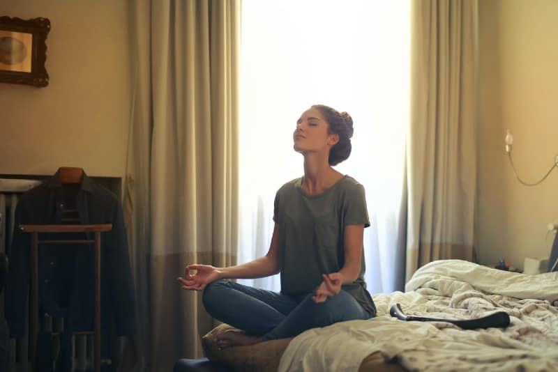 woman meditating while sitting on bed