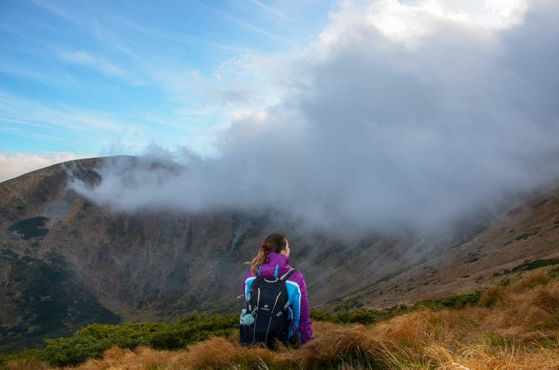 woman on mountain peak with fogs wearing jacket and bringing backpack