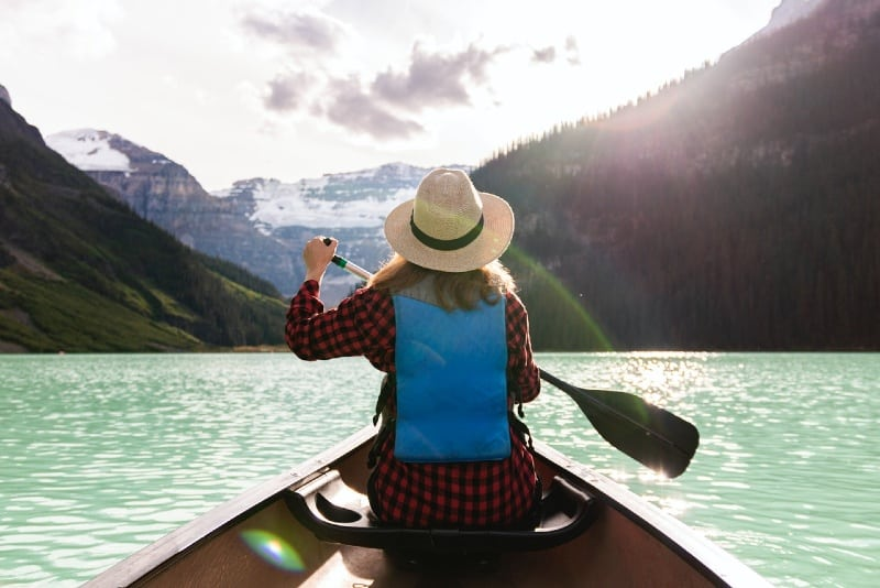 woman with hat paddling a boat in the lake