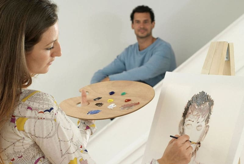 woman painting a portrait of a man sitting at a distant