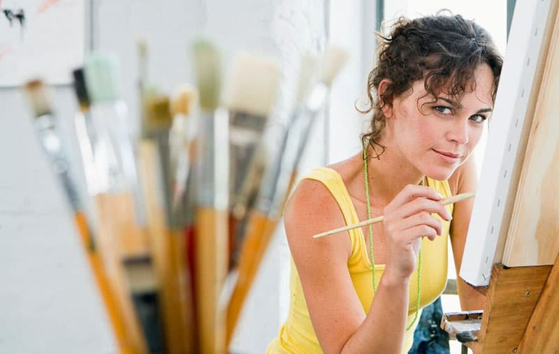 woman painting on canvass inside an art room