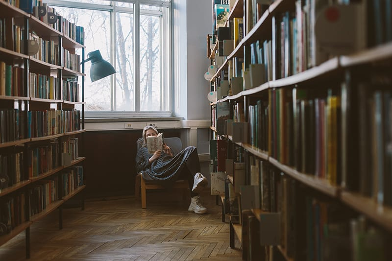 woman reading book while sitting on chair in library