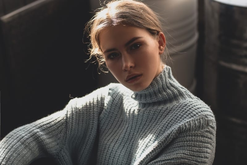 woman in gray sweater sitting indoor