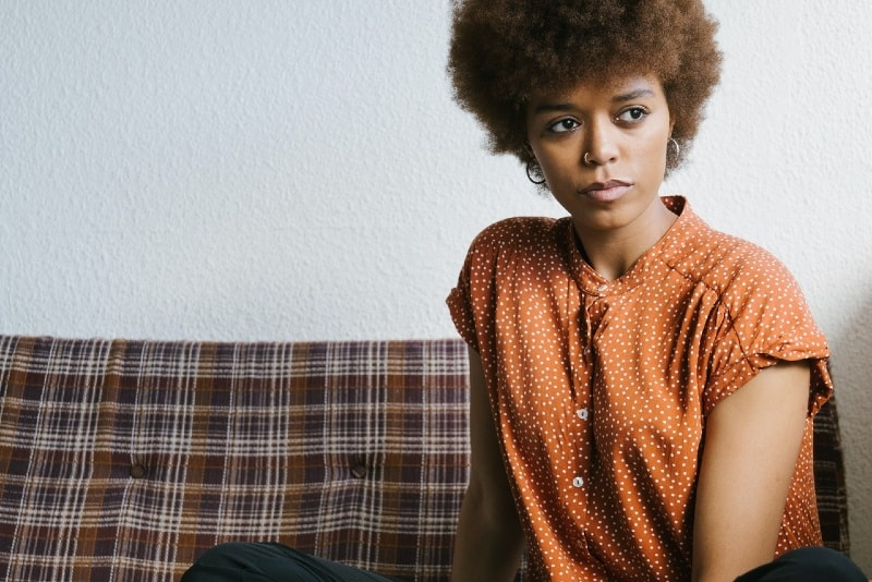 woman in orange top sitting on couch