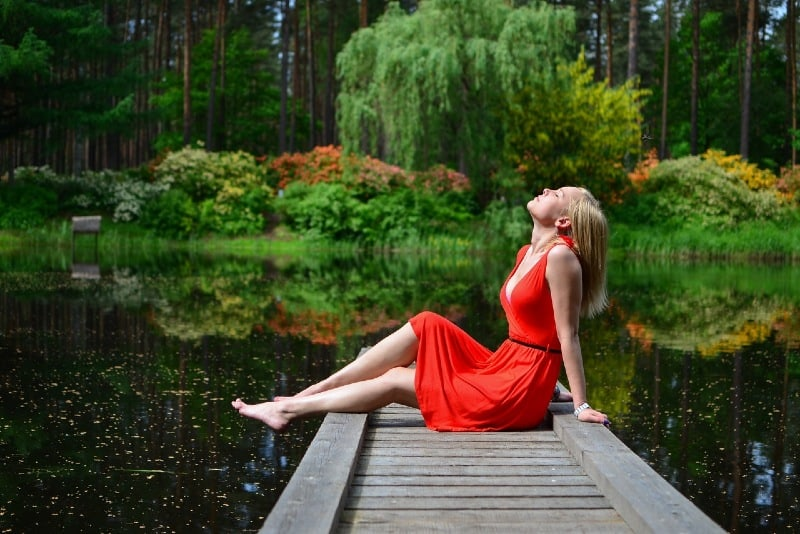 woman in red dress sitting on wooden dock