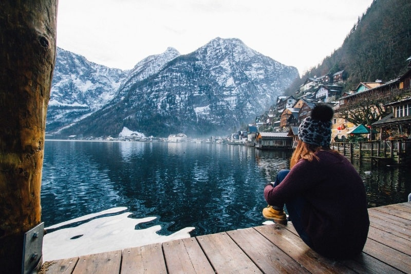 woman in purple sweater sitting on wooden dock