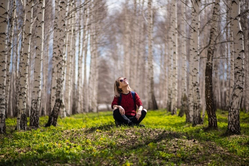 woman with sunglasses sitting on grass near trees