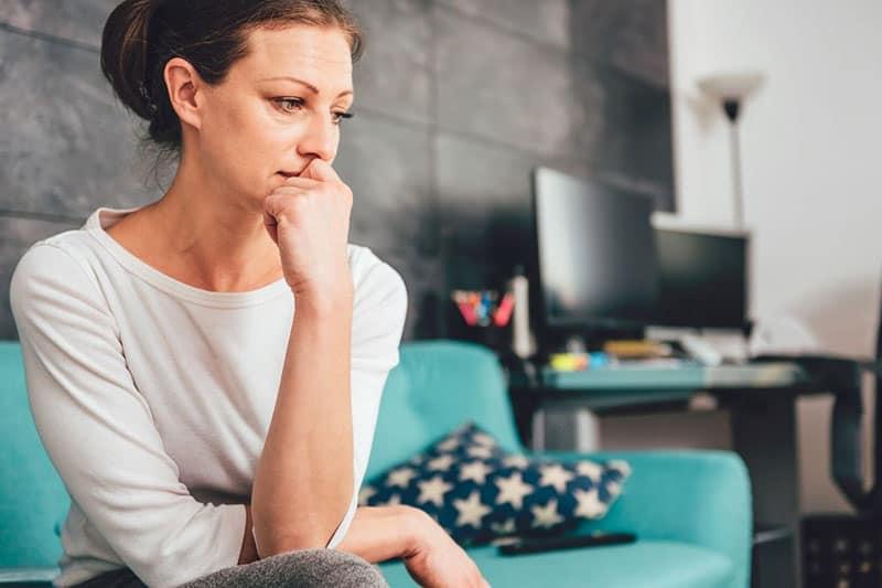 woman sitting on green sofa worried