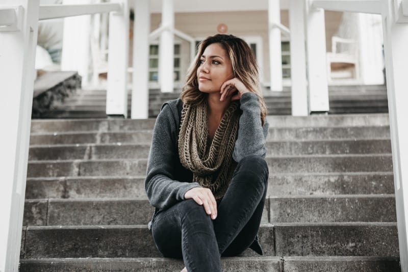 woman with gray scarf sitting on steps