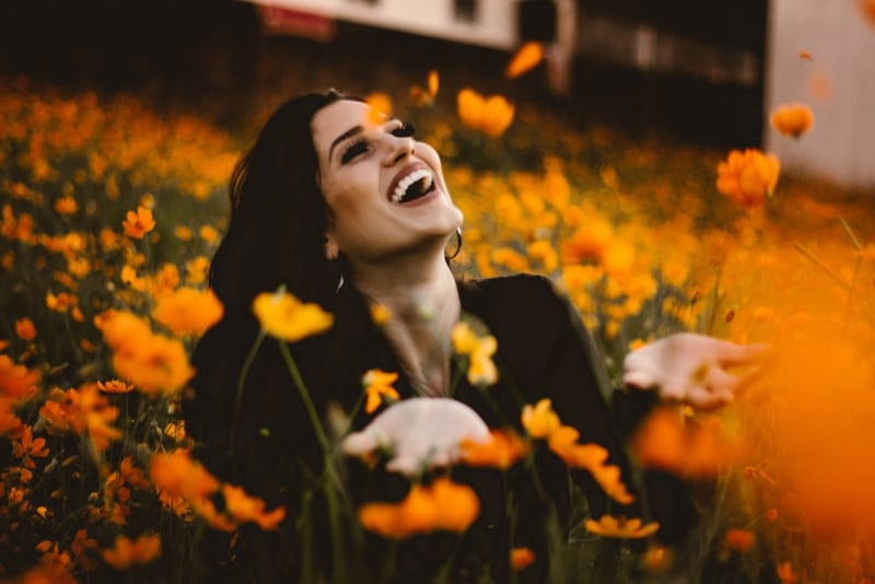 smiling woman sitting on the field near yellow flowers
