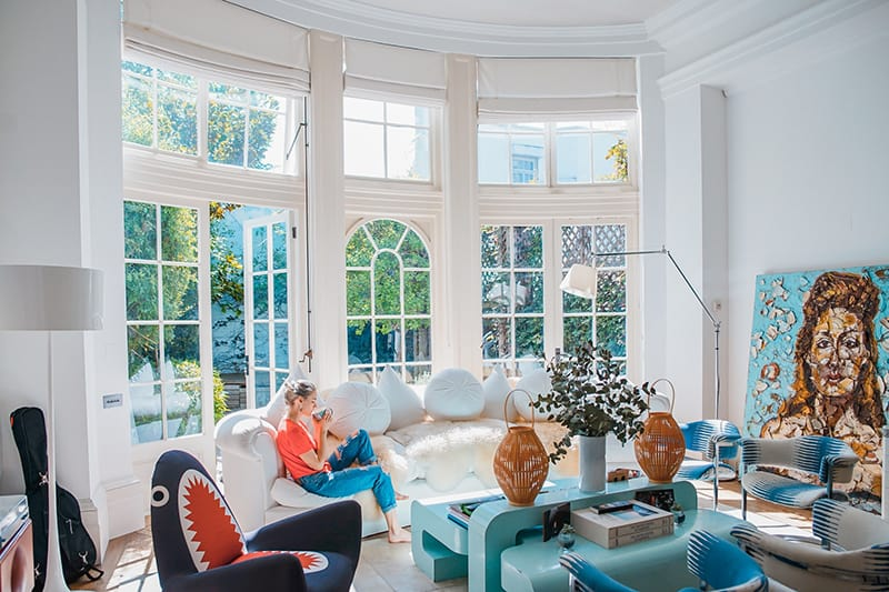 woman sitting on white couch near the window