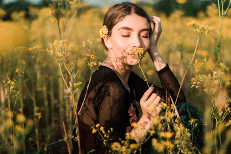 woman in black top smelling yellow flower