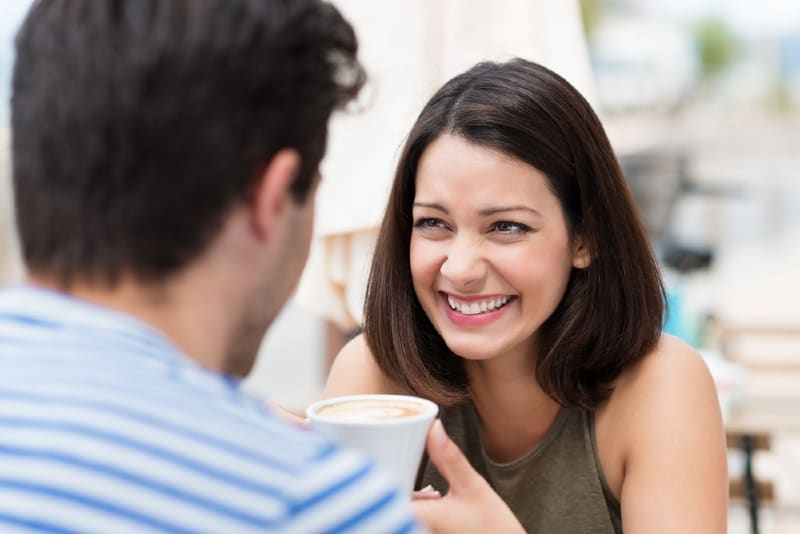 smiling woman looking at man while holding cup of coffee