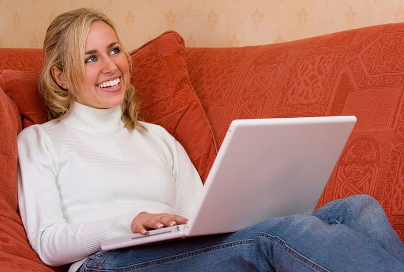 woman smiling while working on laptop sitting on orange couch