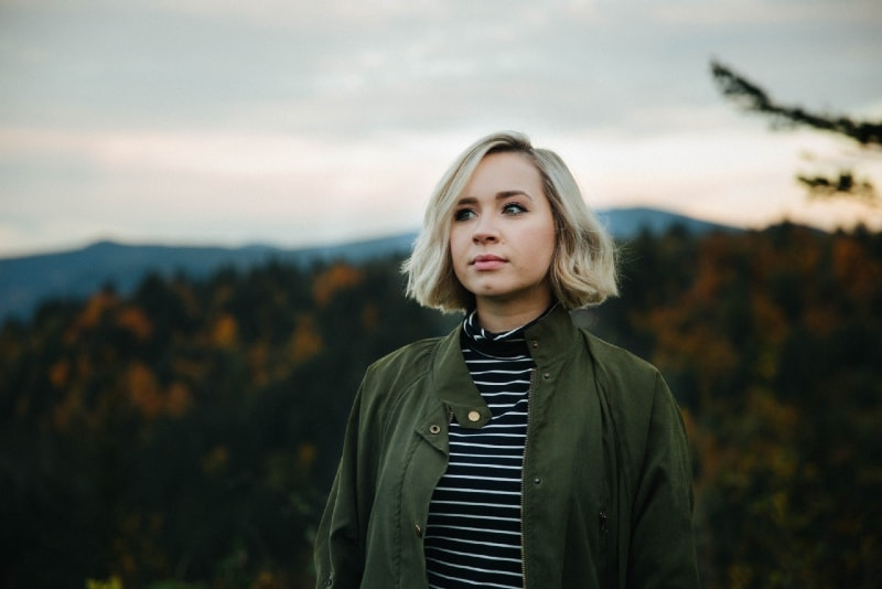 blonde woman in green jacket standing in forest