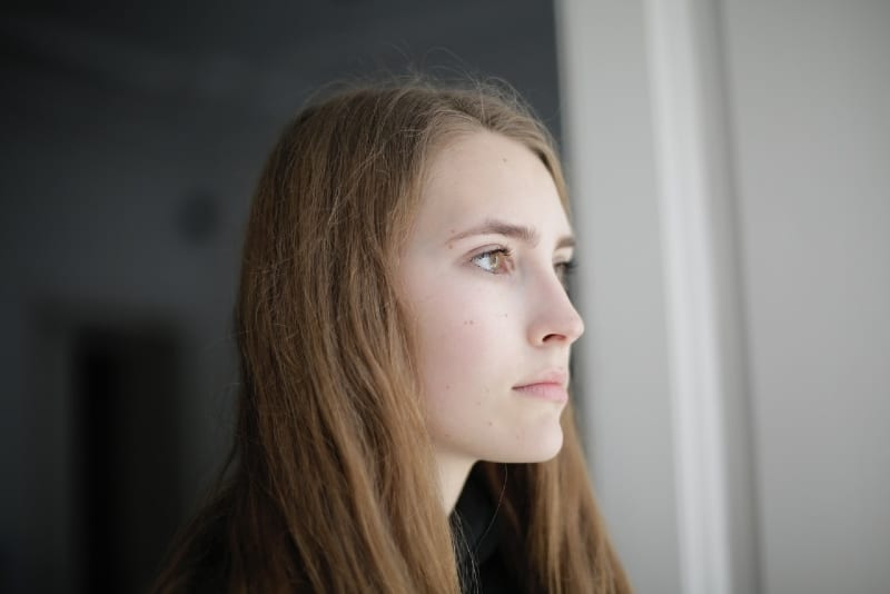 woman standing in living room and thinking