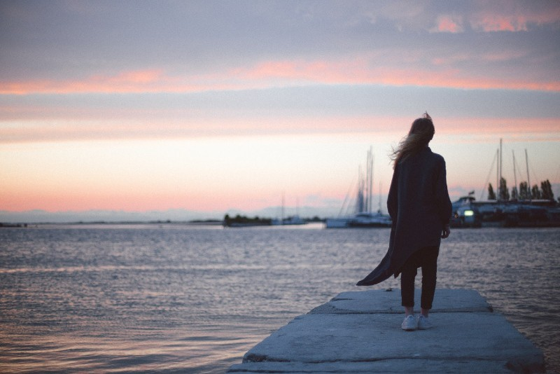 woman in black cardigan standing on dock during sunset