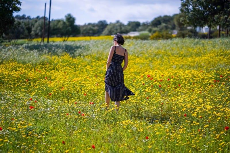 woman in long dress standing in flower field