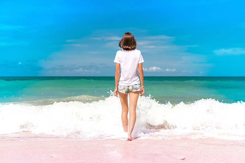 woman standing on seashore facing the water