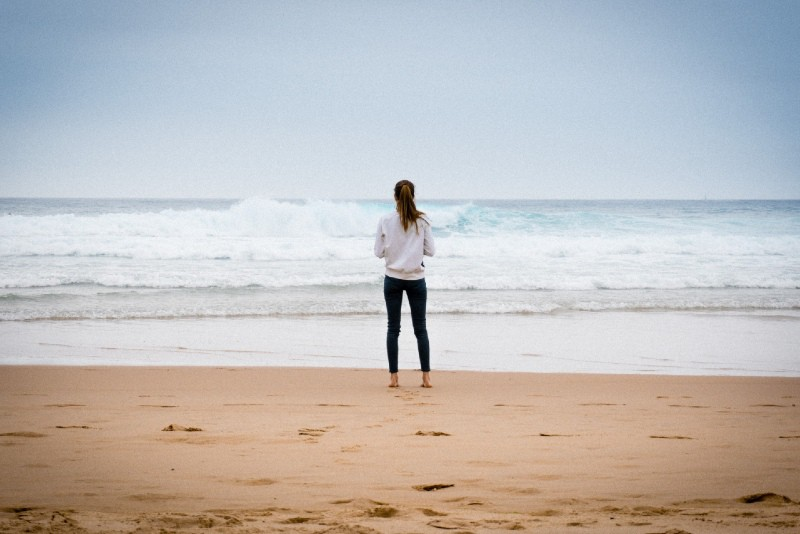 woman standing on shore looking at ocean