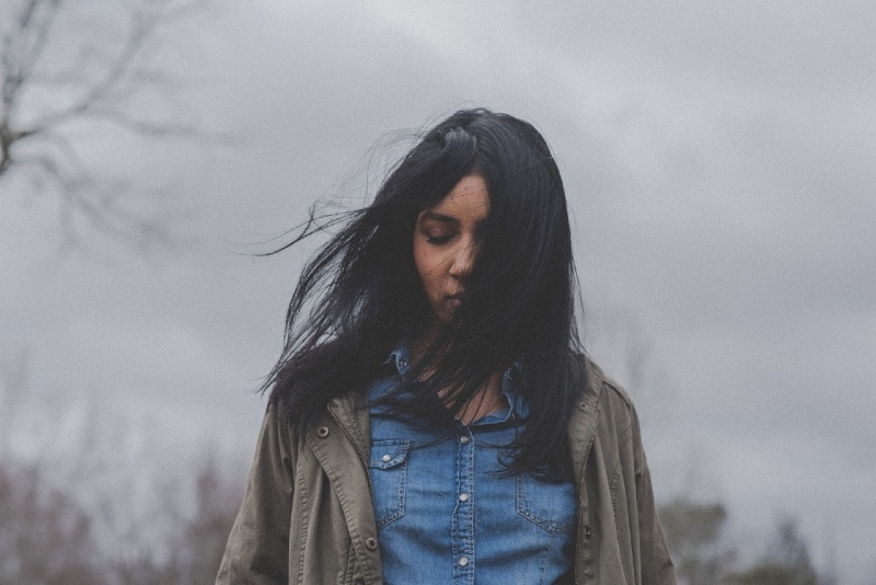 black haired woman in denim shirt standing outdoor