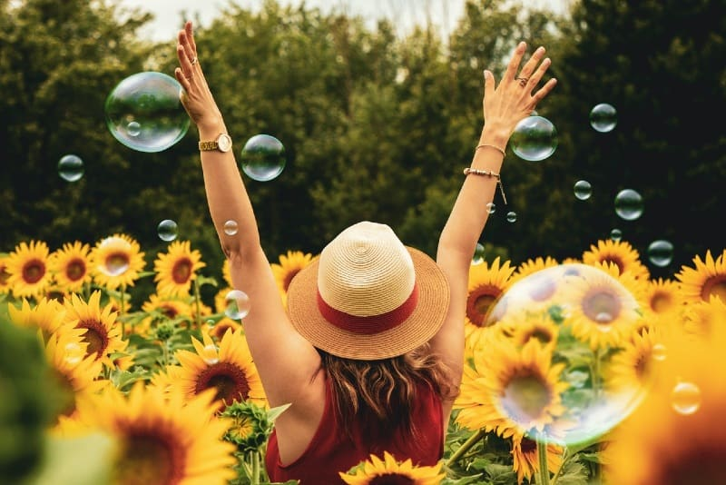 woman with hat standing surrounded by sunflowers