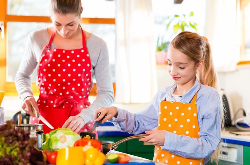 woman teaching kid to cook inside the kitchen with aprons on