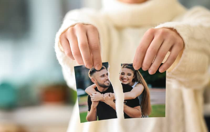 hands of woman tearing photo of happy couple