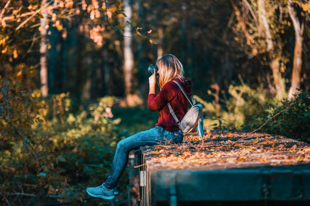 woman using camera while sitting in the nature