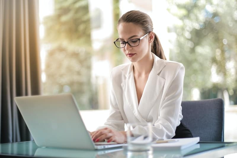 woman with eyeglasses sitting at table and using laptop