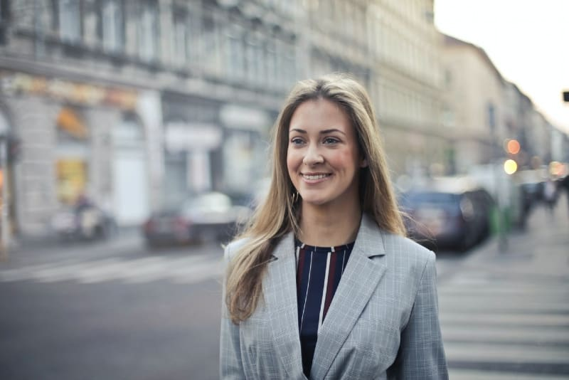 smiling woman in gray coat walking in the street