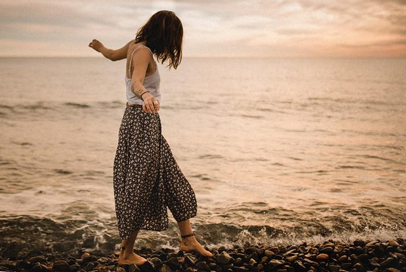 woman walking on rocks near the sea