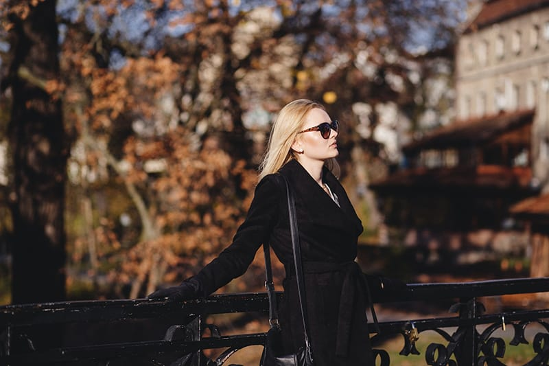 woman wearing black coat leaning on the fence
