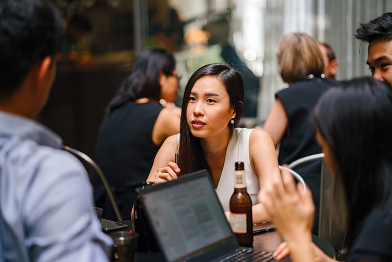 woman wearing white top sitting near table with people