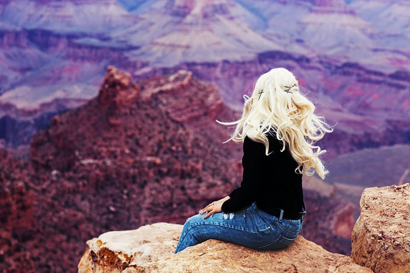 woman with long blonde hair sitting on the cliff