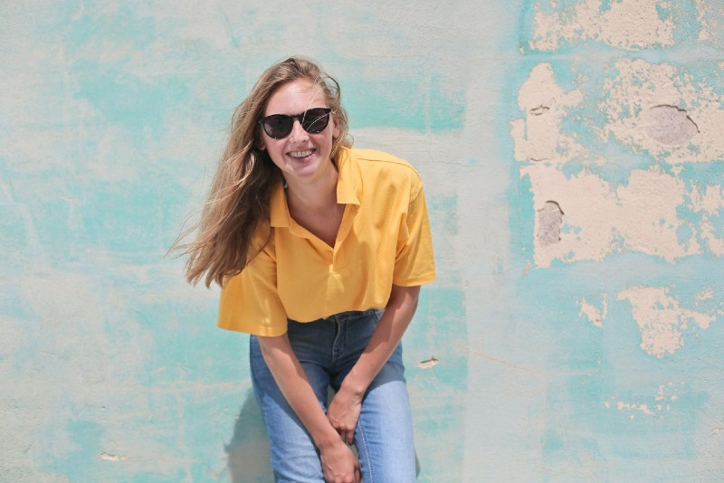 woman with sunglasses wearing yellow top standing near wall