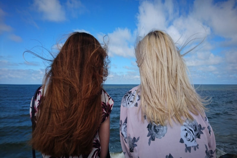 two women looking at sea during daytime