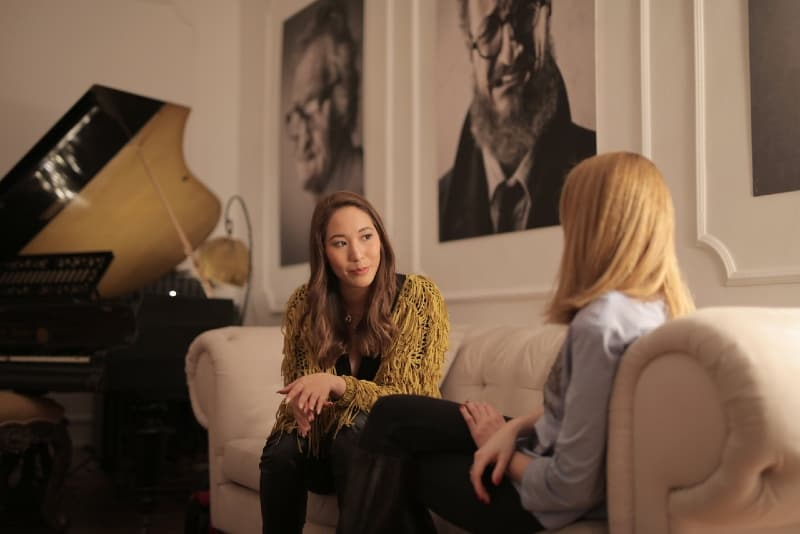 two women sitting on sofa and talking