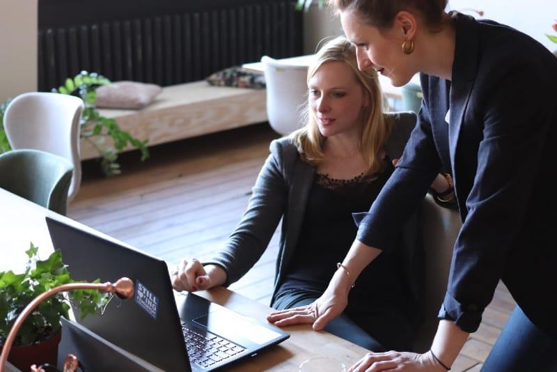 two women using laptop indoor