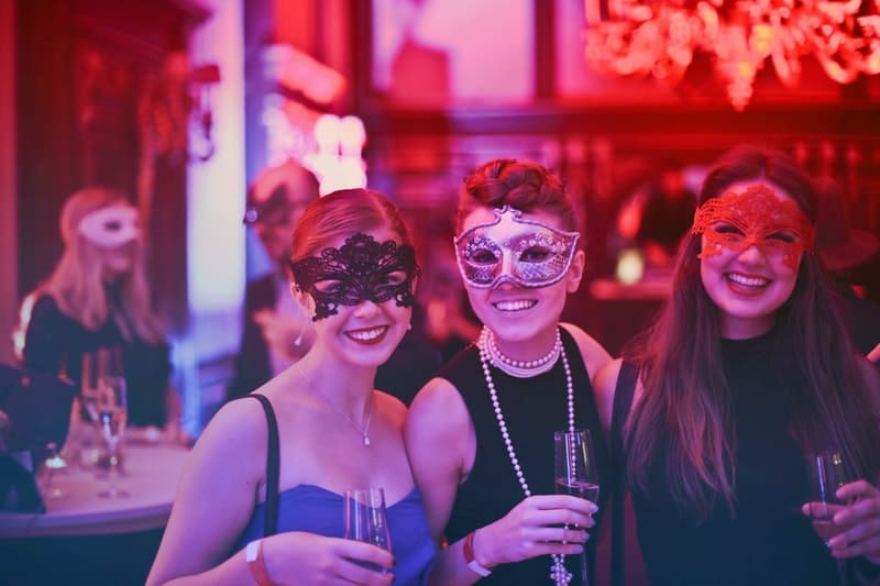 women wearing masks in a party holding wine glasses