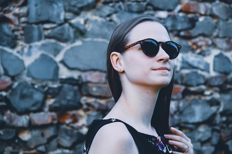 women's wearing black framed sunglasses while touching her hair