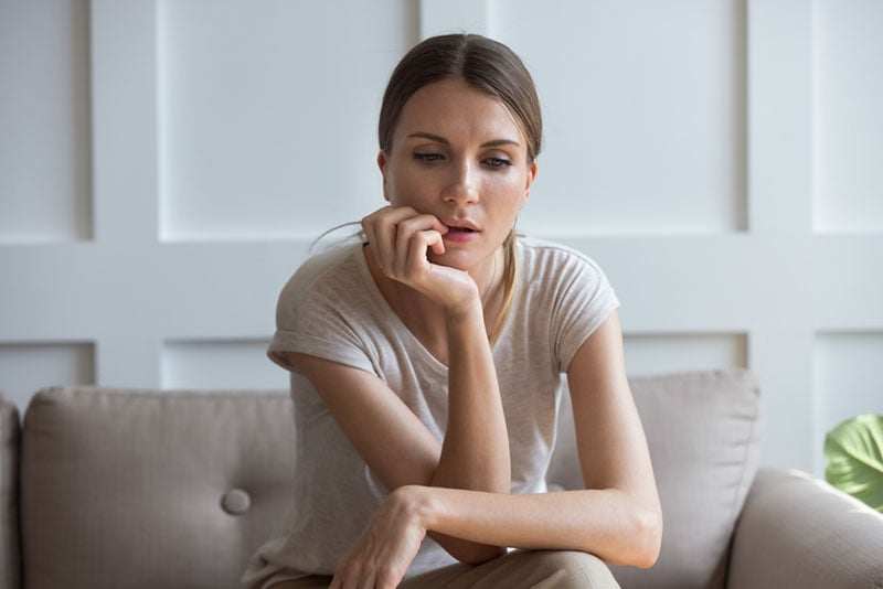 worried young woman sitting on the couch
