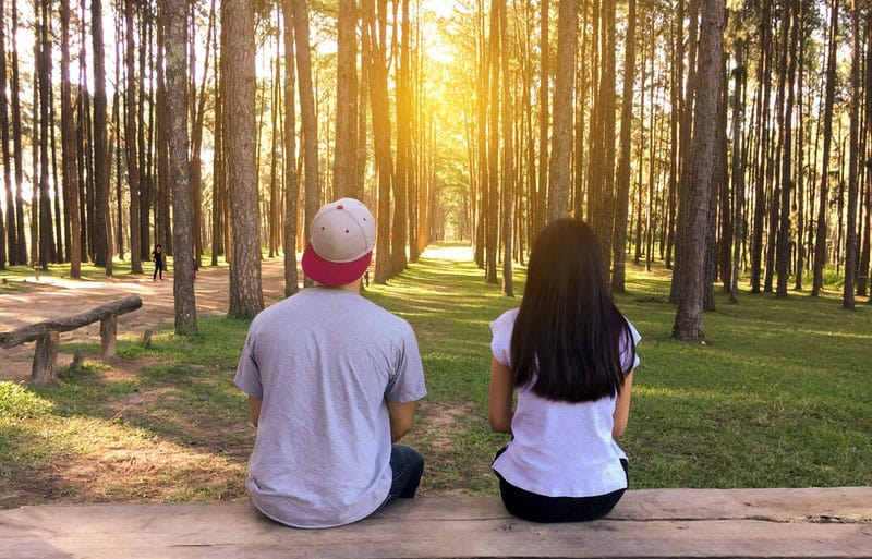 young couple sitting in the wooden bench in the middle of the countryside forest