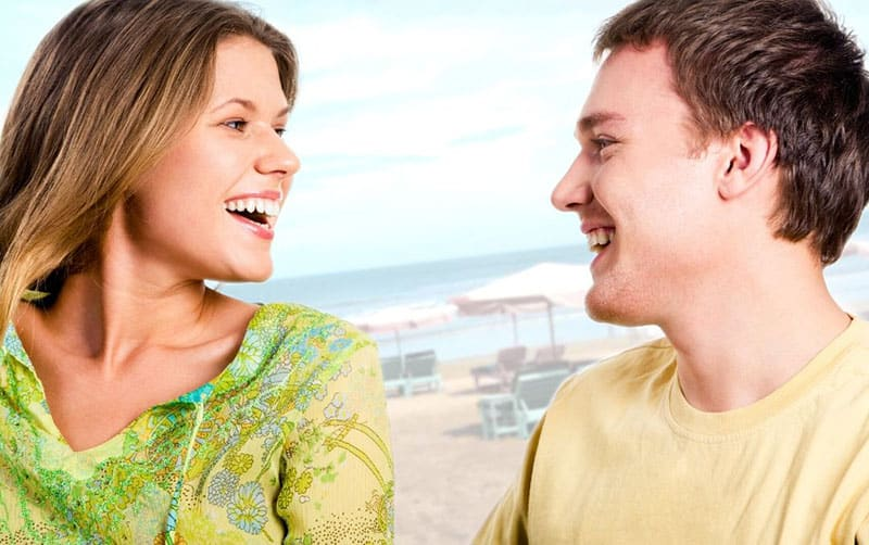 young couple speaking and laughing on the background of the sea