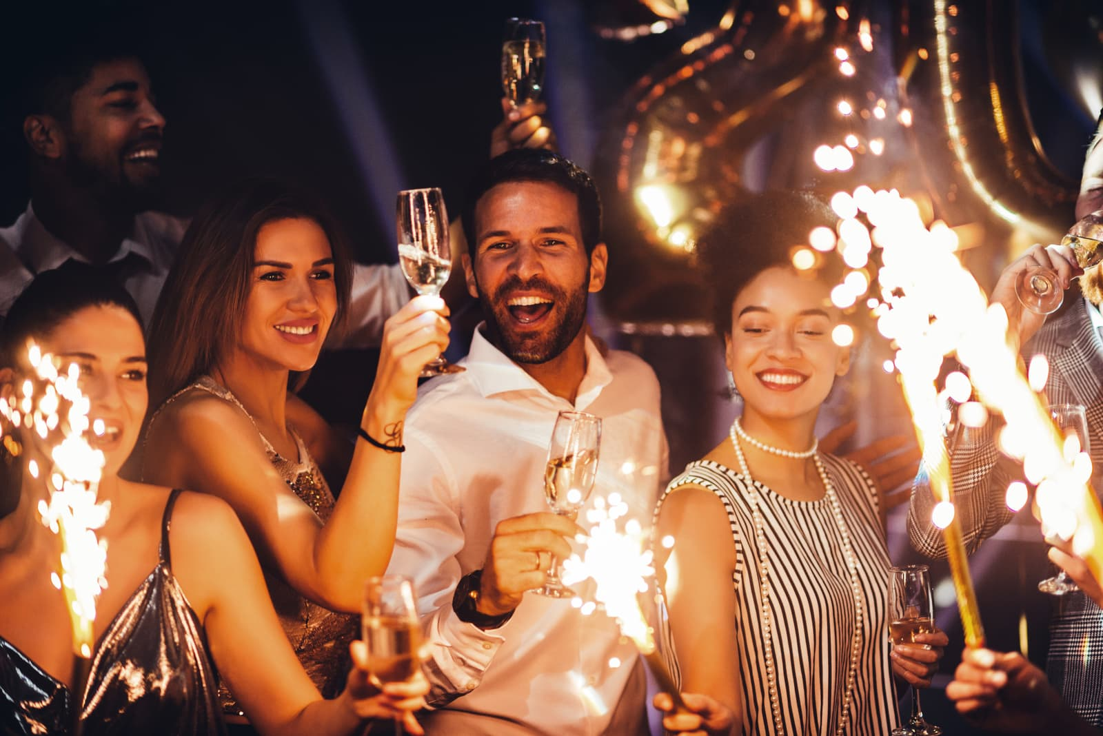 young friends holding sparklers at a party
