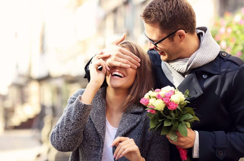 young man surprising woman with flowers and covering her eyes with his hand