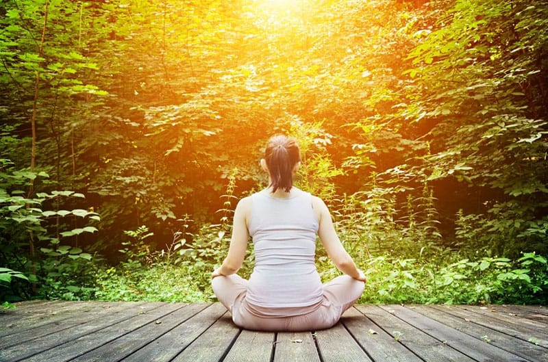 young woman meditates in front of the forest while sitting on wooden floor
